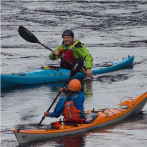 Sea kayak coach and student working together