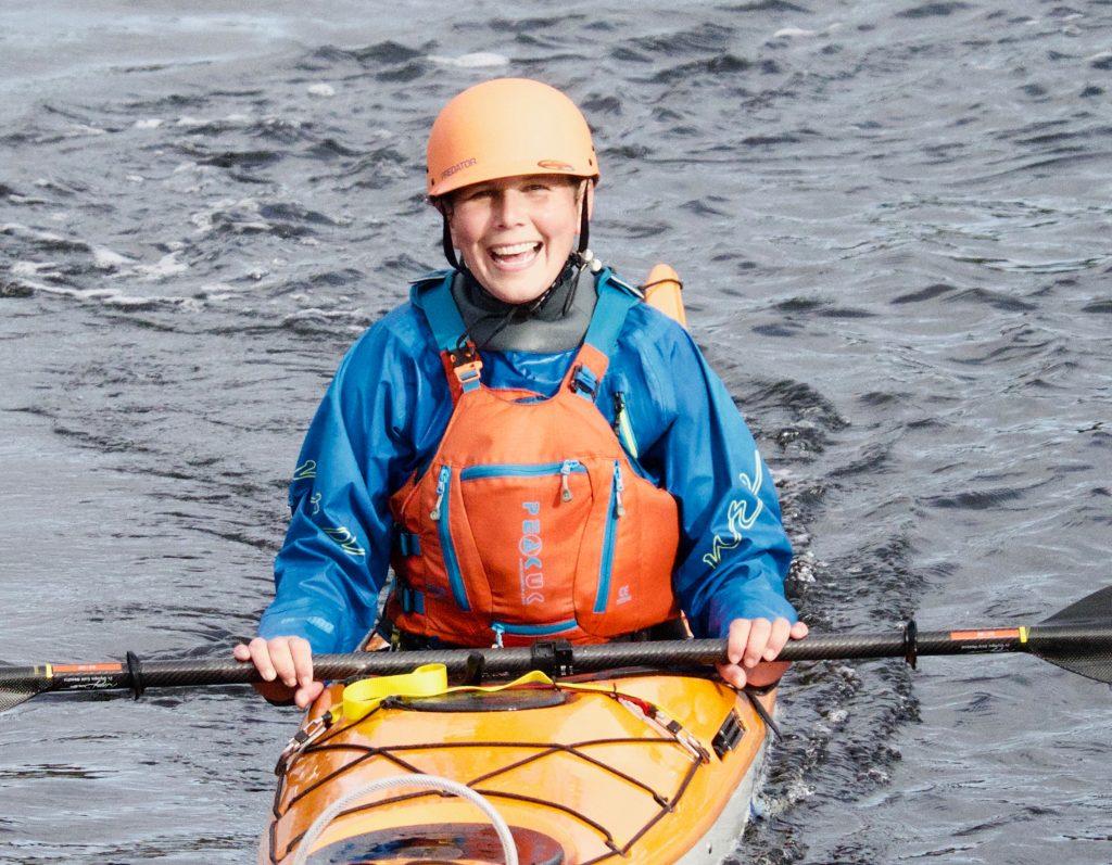 Padder showing Ocean Wrap PFD being worn on the water