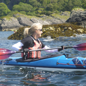 Female kayaker paddling around rock