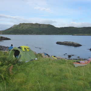 Tent and sea kayak with paddler overlooking islands